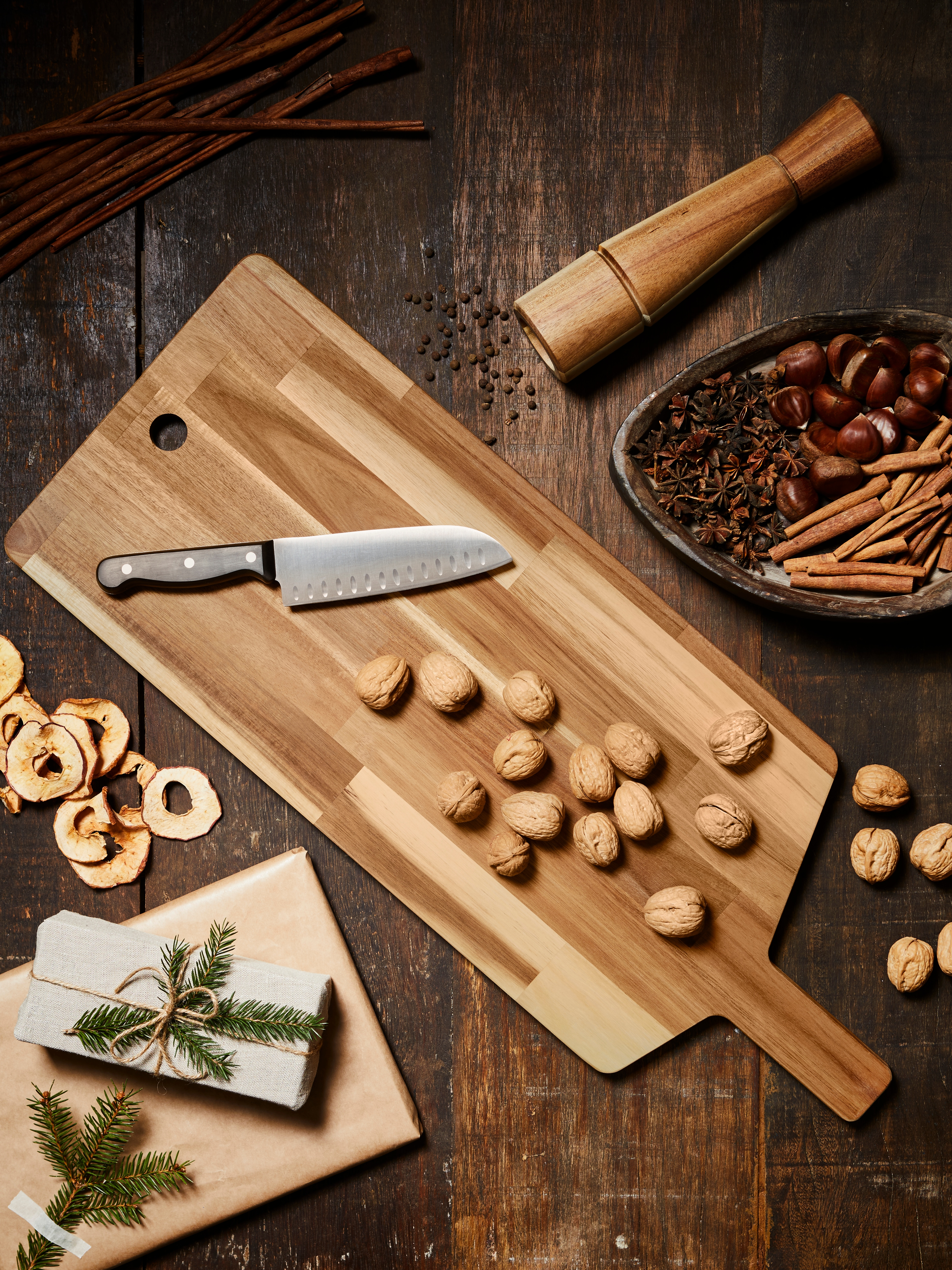 SMÅÄTA wooden chopping board with nuts, spices and dried fruit scattered on wooden surface, kitchen knife and spice mill.