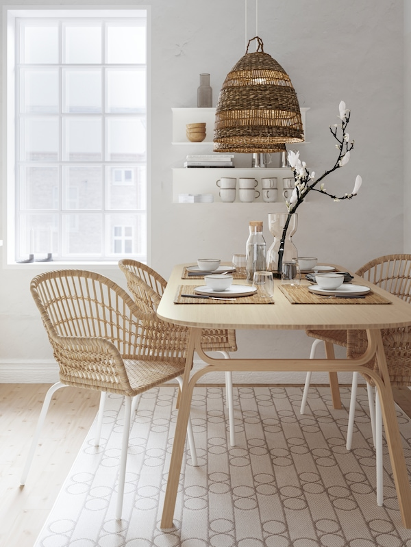 Two NILSOVE rattan armchairs at a VOXLÖV table set with white tableware, beside a window and on top of a white patterned rug.