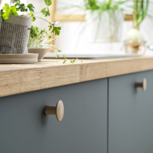 A kitchen with two BODARP drawers in grey-green and a KARLBY worktop in oak veneer. Pots of herbs are sitting on top.