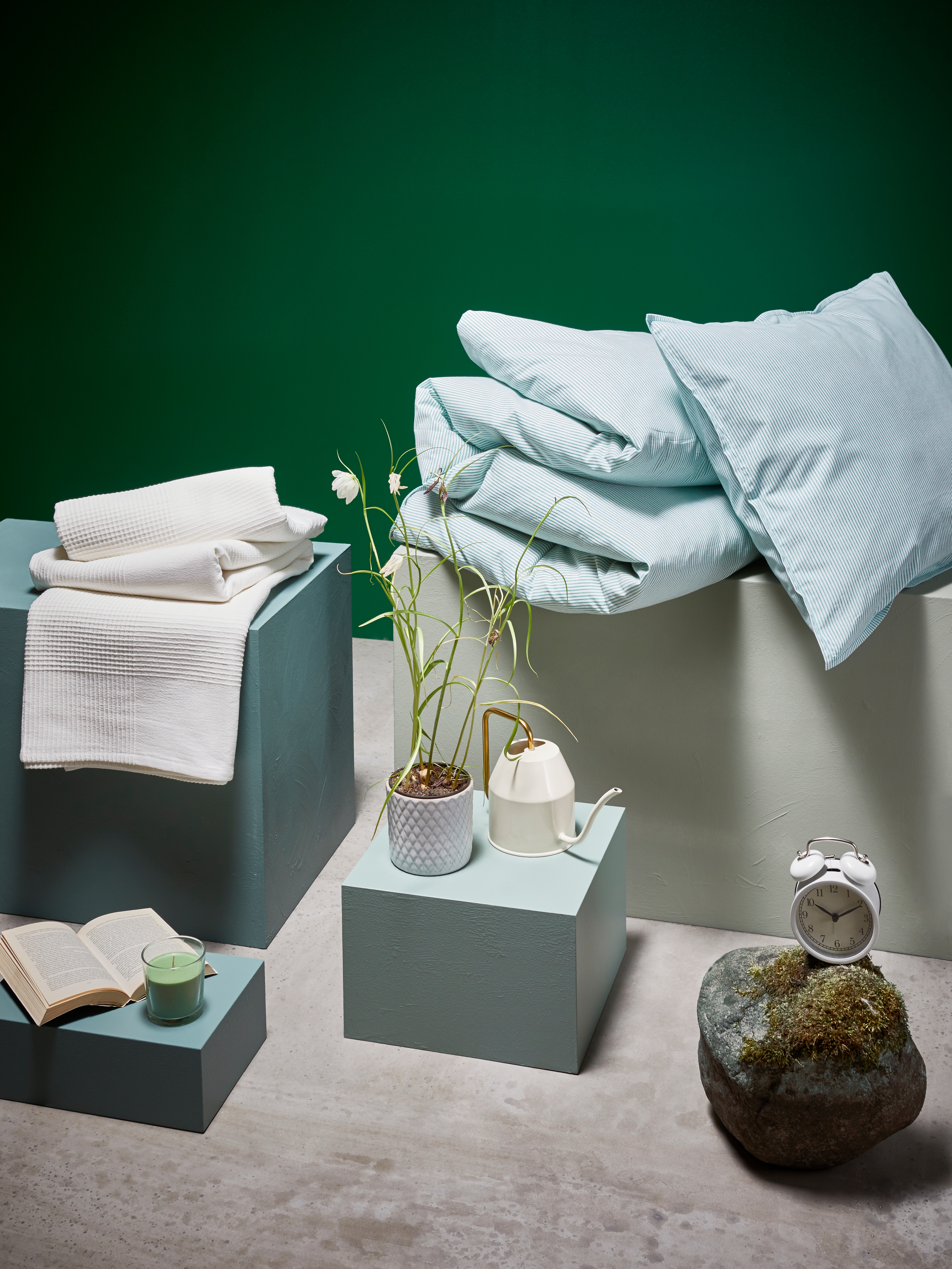 A BERGPALM bed linen set, INDIRA throw, SINNLIG scented candle and VATTENKRASSE watering can, a plant and a clock on podiums.