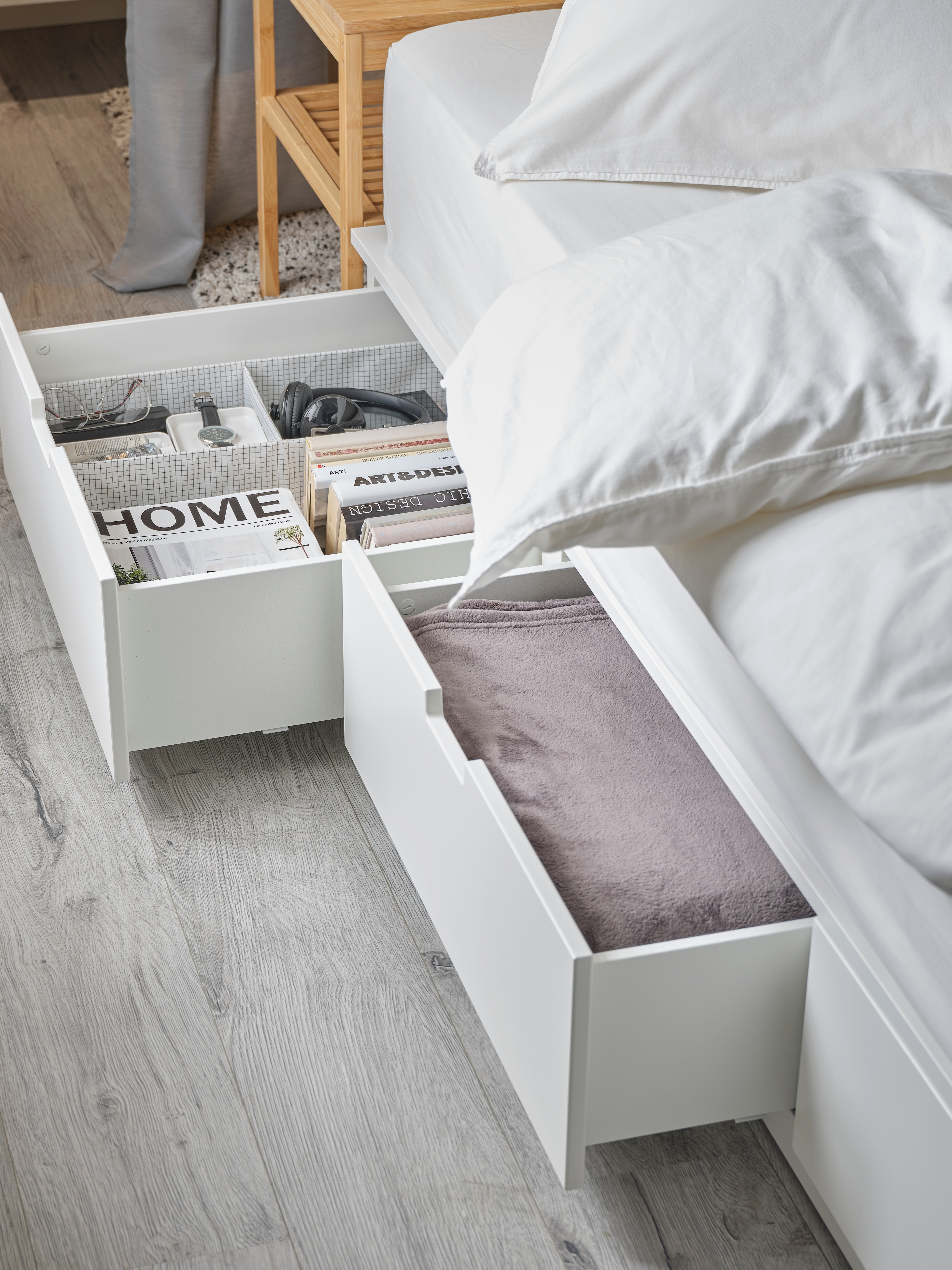 Modern bedroom featuring a bed frame with six drawers, two of each are open revealing a bedspread and magazines.