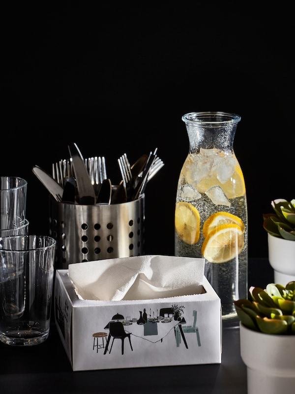 Bicchieri, posate, una caraffa con acqua e fette di limone, una scatola di tovaglioli di carta e due piccole piante - IKEA