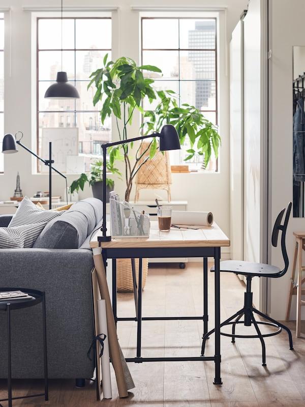 KULLABERG skrivbordsstol och skrivbord, med arbets-/vägglampa fäst i bordsskivan, står bakom en grå soffa.