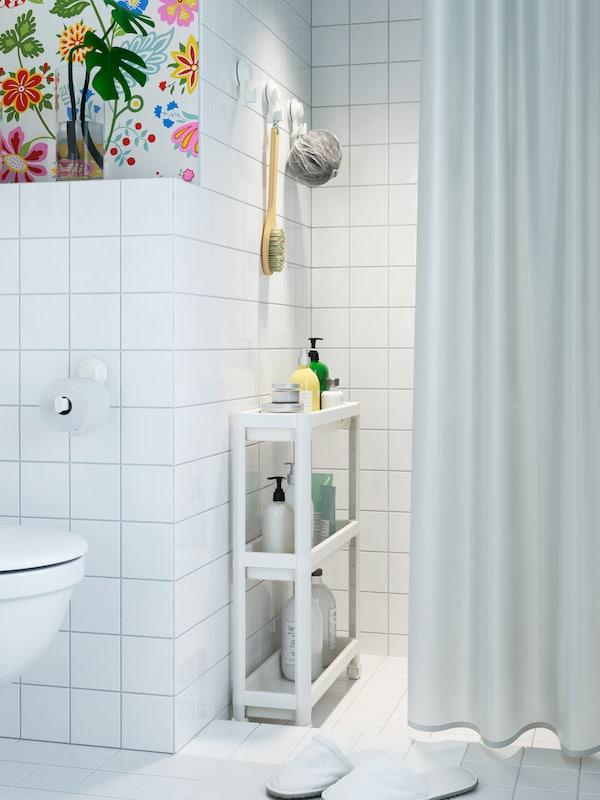 Une salle de bains aux carreaux blancs où se trouve une desserte VESKEN blanche placée sous la pomme de douche.