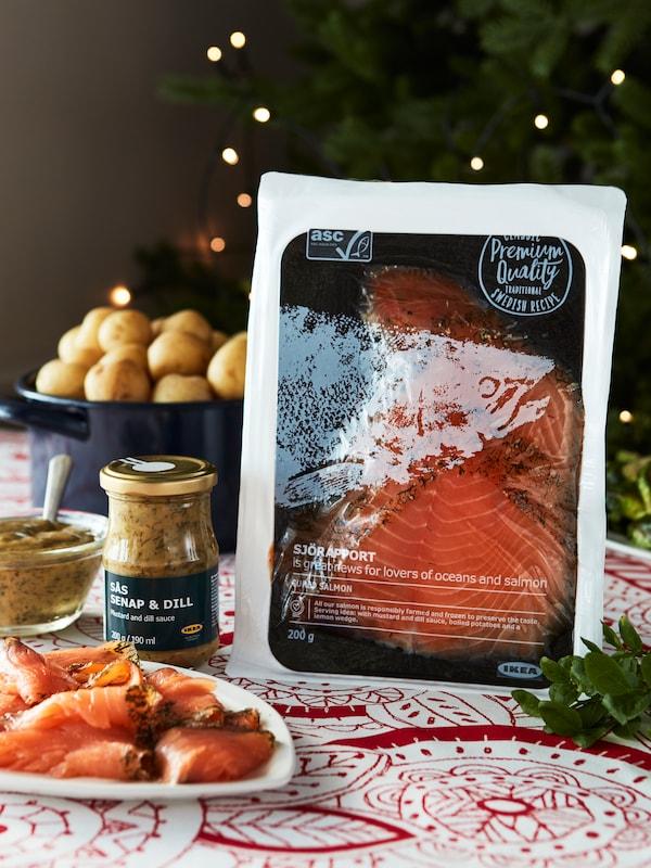 Slavnostní prostírání s balíčkem lososa, hořčice a koprové omáčky ve sklenici, losos na talíři a brambory v hrnci.