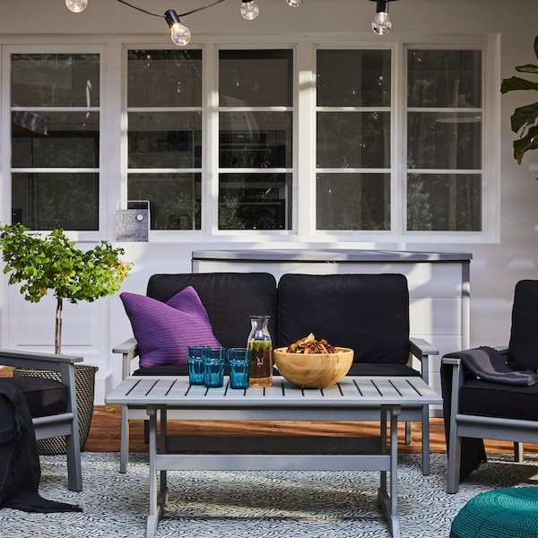 A sofa outside with a grey coffee table holding various items, two outdoor armchairs, a potted plant, windows behind.