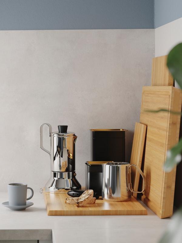 Rohová kuchyňská pracovní deska s bambusovým prkénkem, konvice na přípravu espressa z nerezavějící oceli a dvě černé plechovky na kávu.
