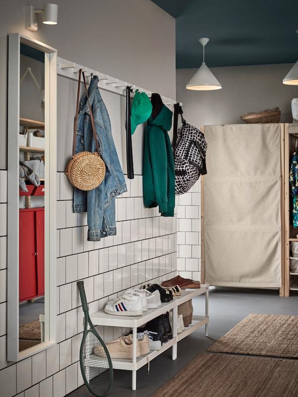 Un couloir avec des patères KUBBIS au mur où sont pendus des manteaux, des chapeaux et des sacs, au-dessus de range-chaussures MACKAPÄR contenant des chaussures et des bottes.