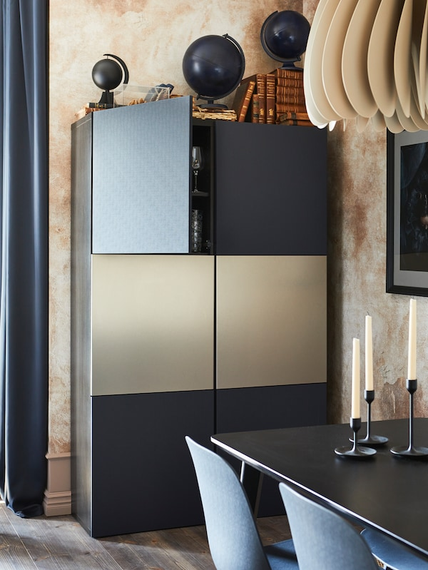 BESTÅ cabinets with doors of different colours are attached to a wall near a black LISABO table with candles on top.