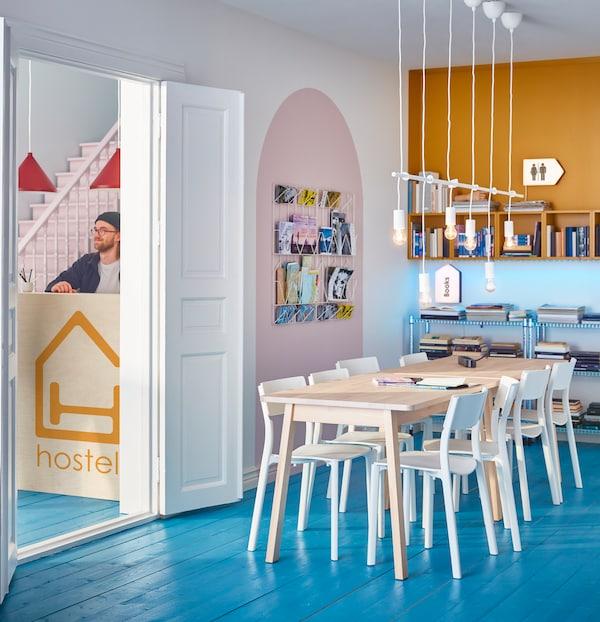 Prostor za druženje v hostlu z dolgo mizo, belimi stoli in visečimi svetilkami. Skozi vrata se vidi recepcija.