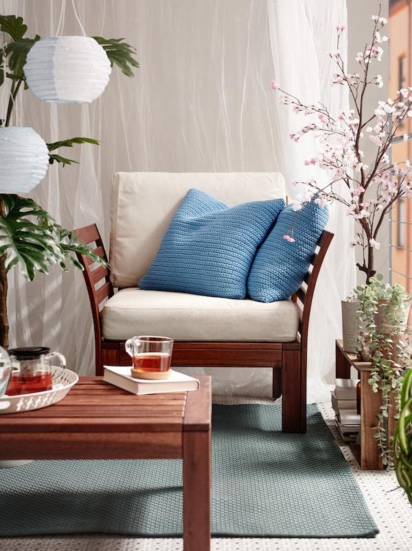 sur un balcon est placé un fauteuil de jardin avec des coussins bleus et une table basse de jardin. Les deux éléments sont sur un tapis d'extérieur vert.