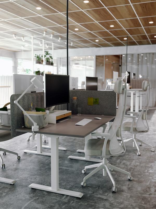 Spazio di lavoro diviso da paraventi in feltro, scrivanie marroni e bianche, sedie da ufficio in beige/bianco, PC e lampade da tavolo bianche.
