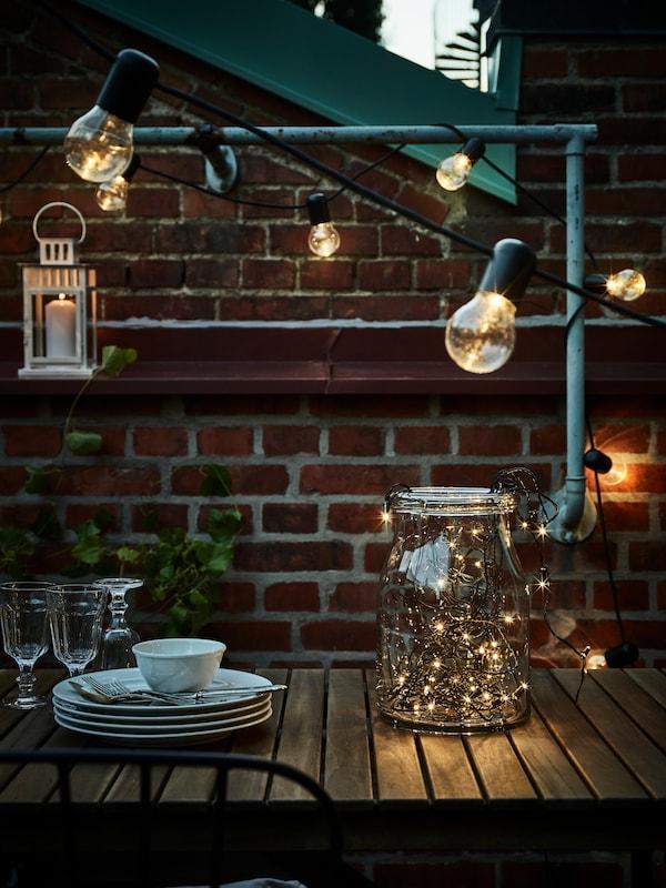 Asztal egy kültéri részen, tányérokkal, evőeszközökkel, poharakkal és egy dekoratív üveggel, sok függő világítással és egy lámpával.