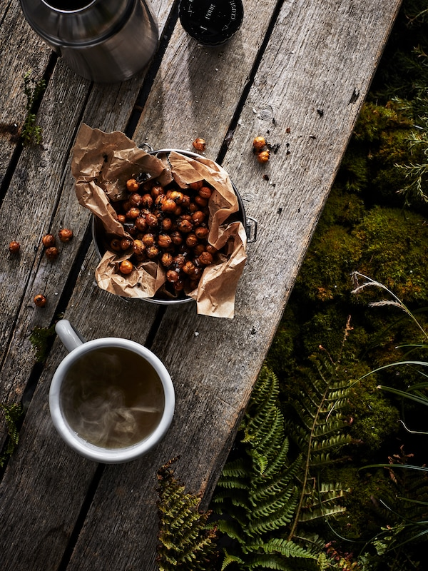 A cup of EGENTID tea beside a bowl of chai and chilli roasted chickpeas and an open thermos flask on a wooden table.