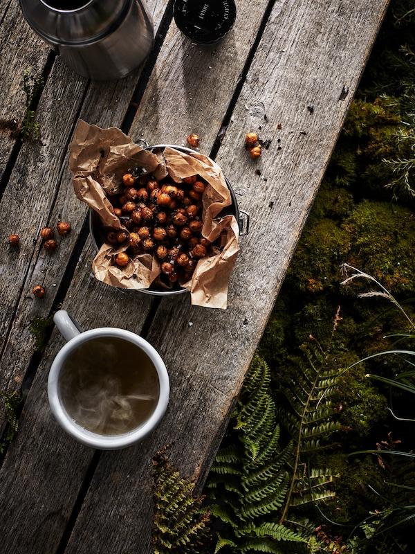 Na drevenom stole je položená šálka čaju EGENTID vedľa misky s cícerom s príchuťou Chai a čili, pri nej stojí otvorená termoska.