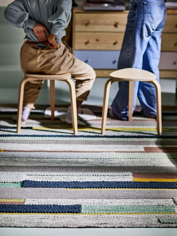 A multicolour BRÖNDEN rug with two birch stools on top, with one person standing and another sitting and storage behind.