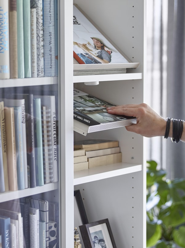 IKEA BOTTNA light beige display mesh shelves installed in a white BILLY bookcase, holding books.