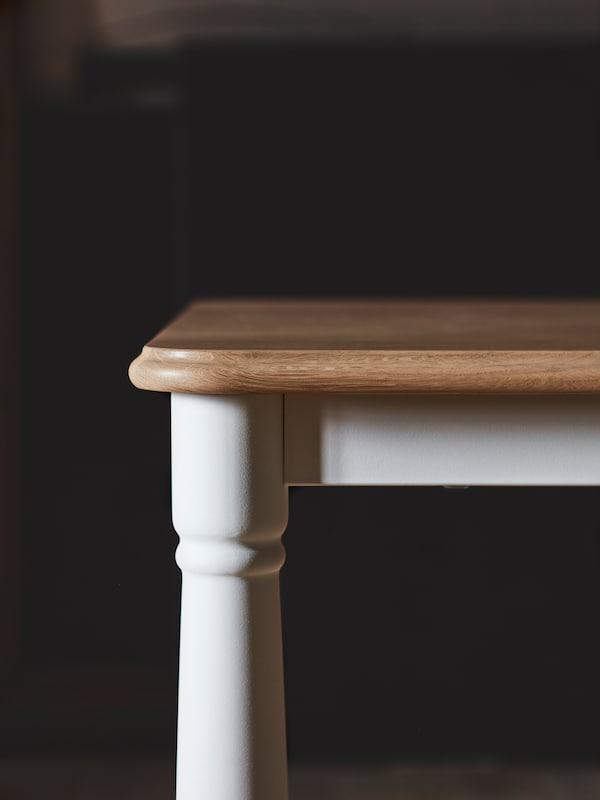 Es ist die Ecke eines DANDERYD Esstischs mit einer hellen Tischplatte aus Holz und weißen Beinen zu sehen, die wie traditionell gedrechselte Beine geformt sind.