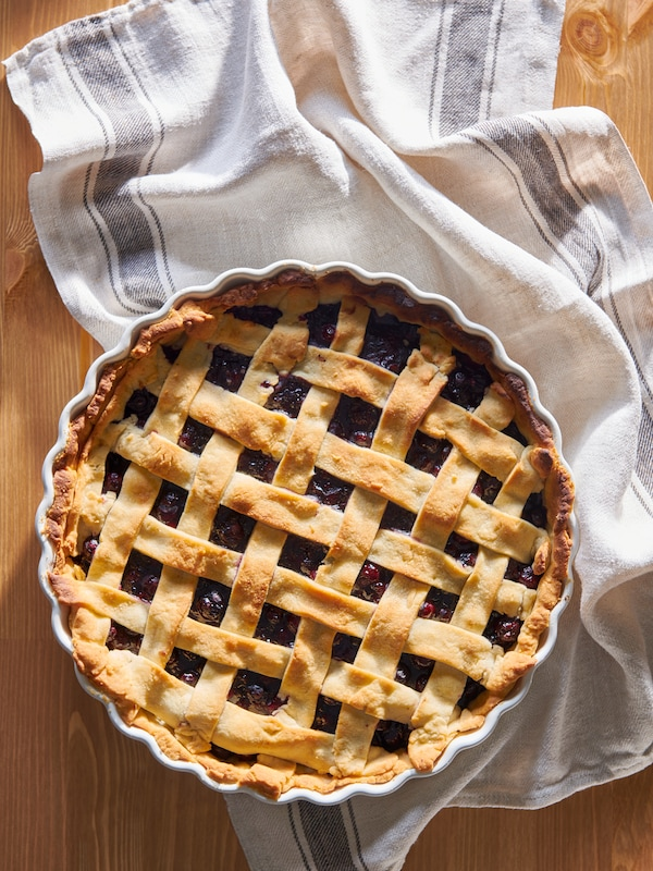A golden brown dessert pie, in a VARDAGEN pie dish, is resting on a beige tea towel with stripes, on a wooden worktop.