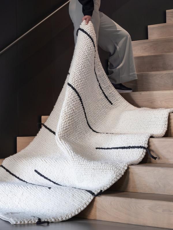 階段に立っている人が、ホワイトと黒の手織りのLOKALT/ロカルト ウール ラグの端を持っている。