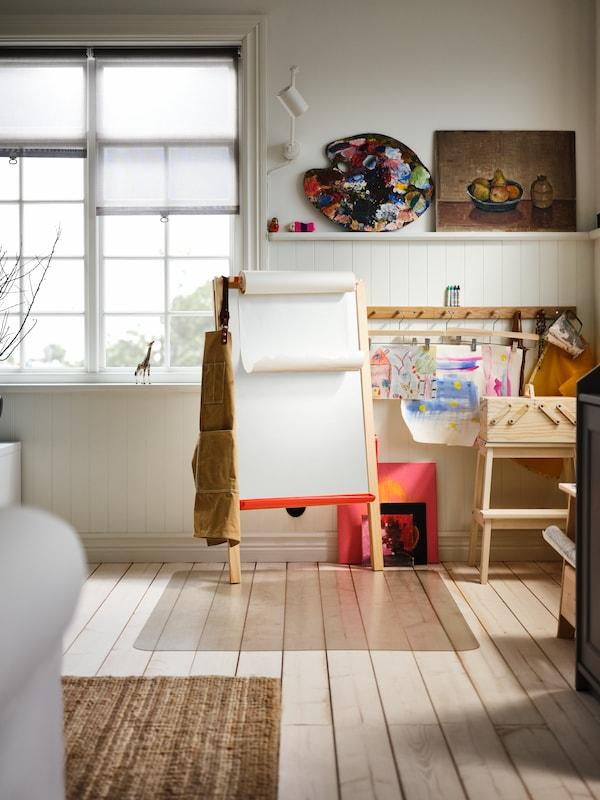 In einem Kinderzimmer steht eine Maltafel von IKEA neben einem Kinderschreibtisch und hinter zwei Kinderhockern von IKEA.