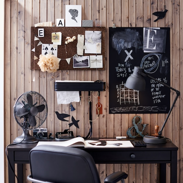 A workspace with a dark academia aesthetic, including a black desk, a gray table lamp, a chalkboard, vintage decor, and a cork memo board with various photos and decorative images.