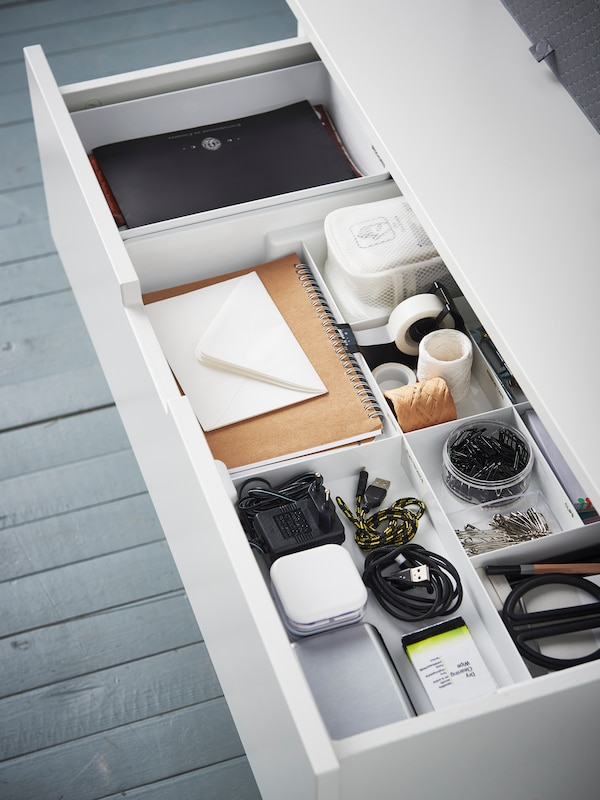 A white storage unit with the drawer open, holding files, boxes, and assorted containers plus other diverse items.