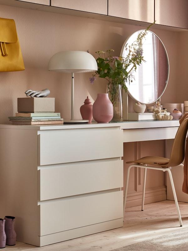 Um toucador e uma cómoda MALM em branco, encostados a uma parede, com um espelho para toucador VENNESLA e um candeeiro.