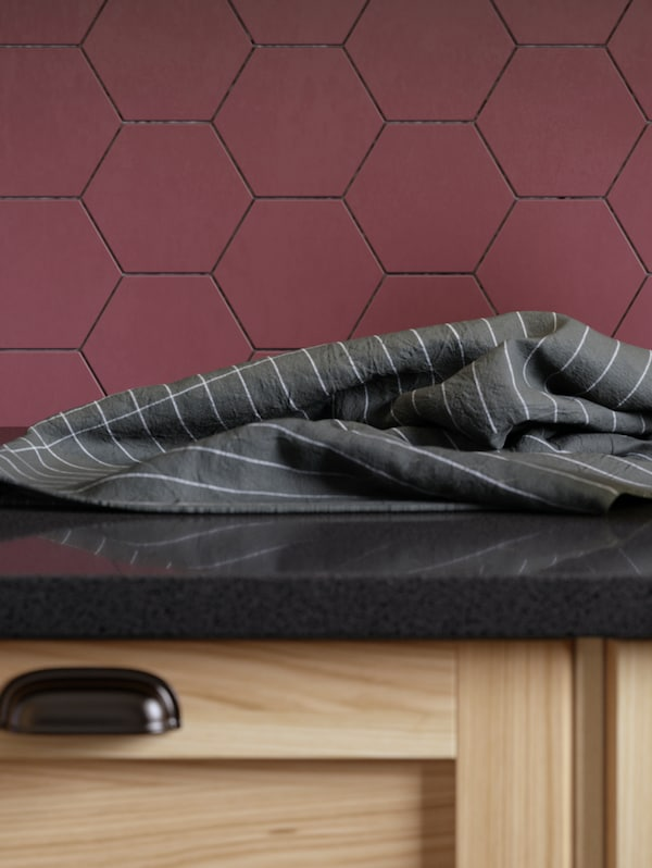 A wooden kitchen cabinet below a dark grey worktop and a purple wall panel. A tea towel is on the worktop.