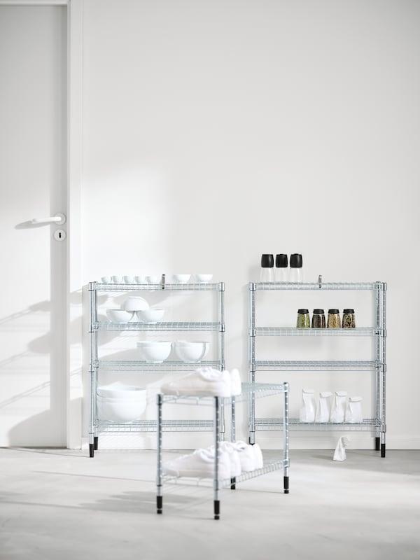Tres estanterías OMAR a diferentes alturas junto a una pared blanca: una tiene cuencos; otra, tarros, y la tercera, zapatillas blancas.