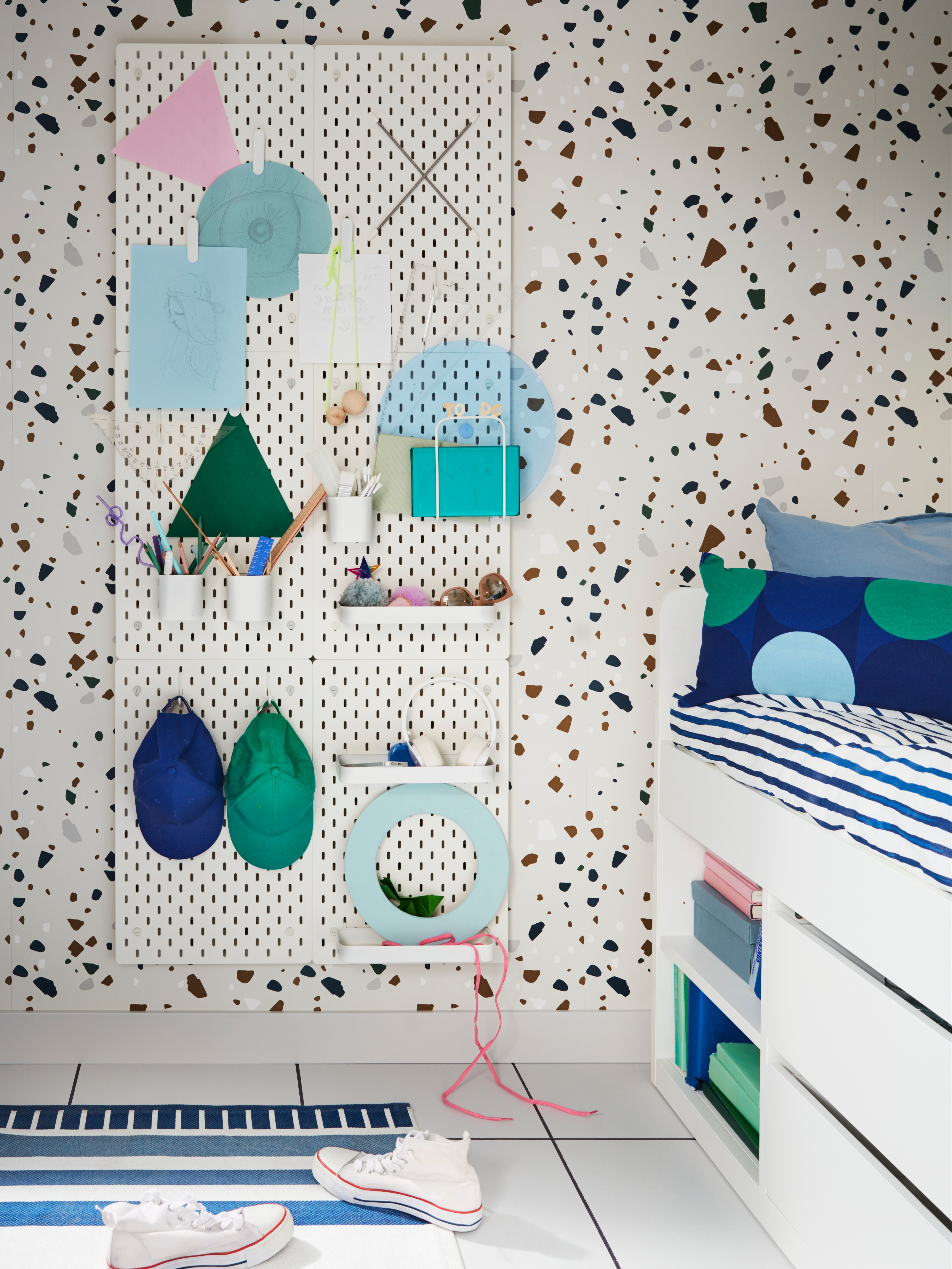 A wall with three rows of two SKÅDIS white pegboards, containers and shelves holding a tablet, headphones and more by a bed.