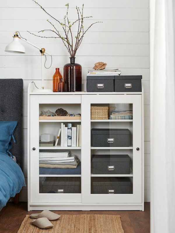 Dark grey TJOG storage boxes inside a white HAUGA glass-door cabinet with small items placed next to a dark blue bed.