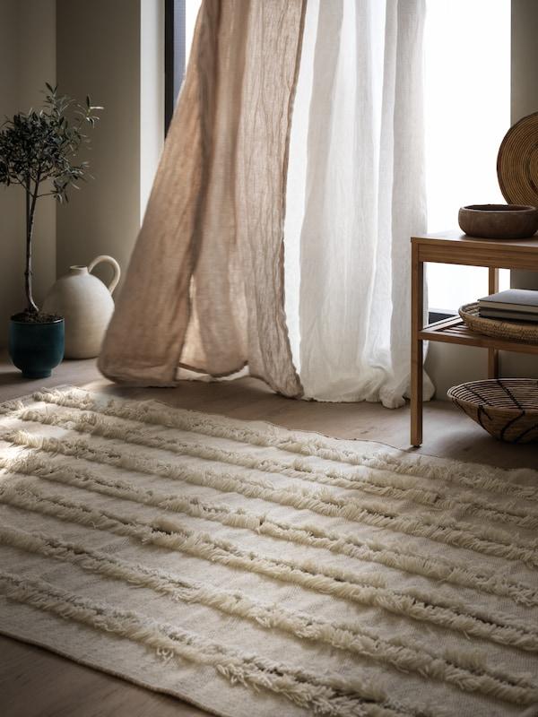 Hladce tkaný koberec PEDERSBORG umístěný ve vzdušné a příjemně osvětlené místnosti před velkými okny se závěsy vlajícími ve větru.