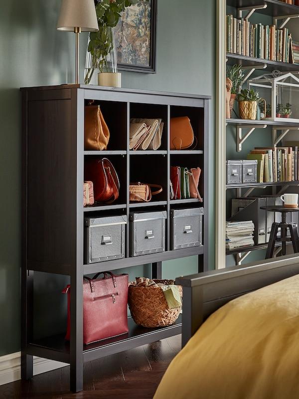 Des sacs et des boîtes sur les tablettes d'une unité de rangement noir-brun HEMNES placée contre le mur d'une chambre à coucher.