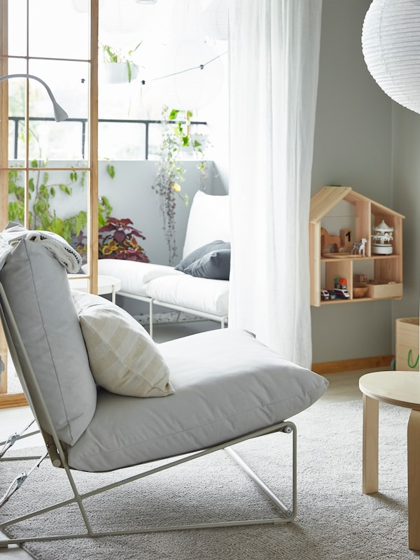 Un scaun ușor într-o cameră de zi și o canapea cu 2 locuri pe un balcon – pot fi folosite atât la interior, cât și la exterior.