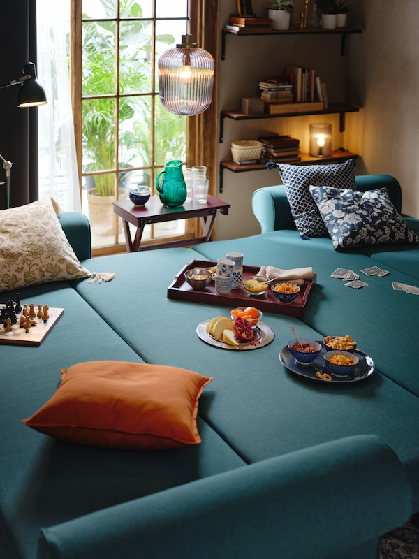 Food on plates and a dark-red MARYD tray placed on two folded-out, dark-turquoise VRETSTORP sofa-beds pushed together.