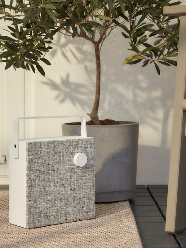 Ein ENEBY Bluetooth-Lautsprecher auf einem beigefarbenen Teppich neben einem Sessel