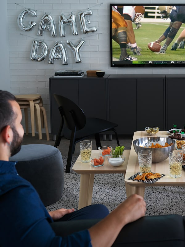 A man watches sport on TV in a living room, with drinks and snacks set out on LISABO tables.