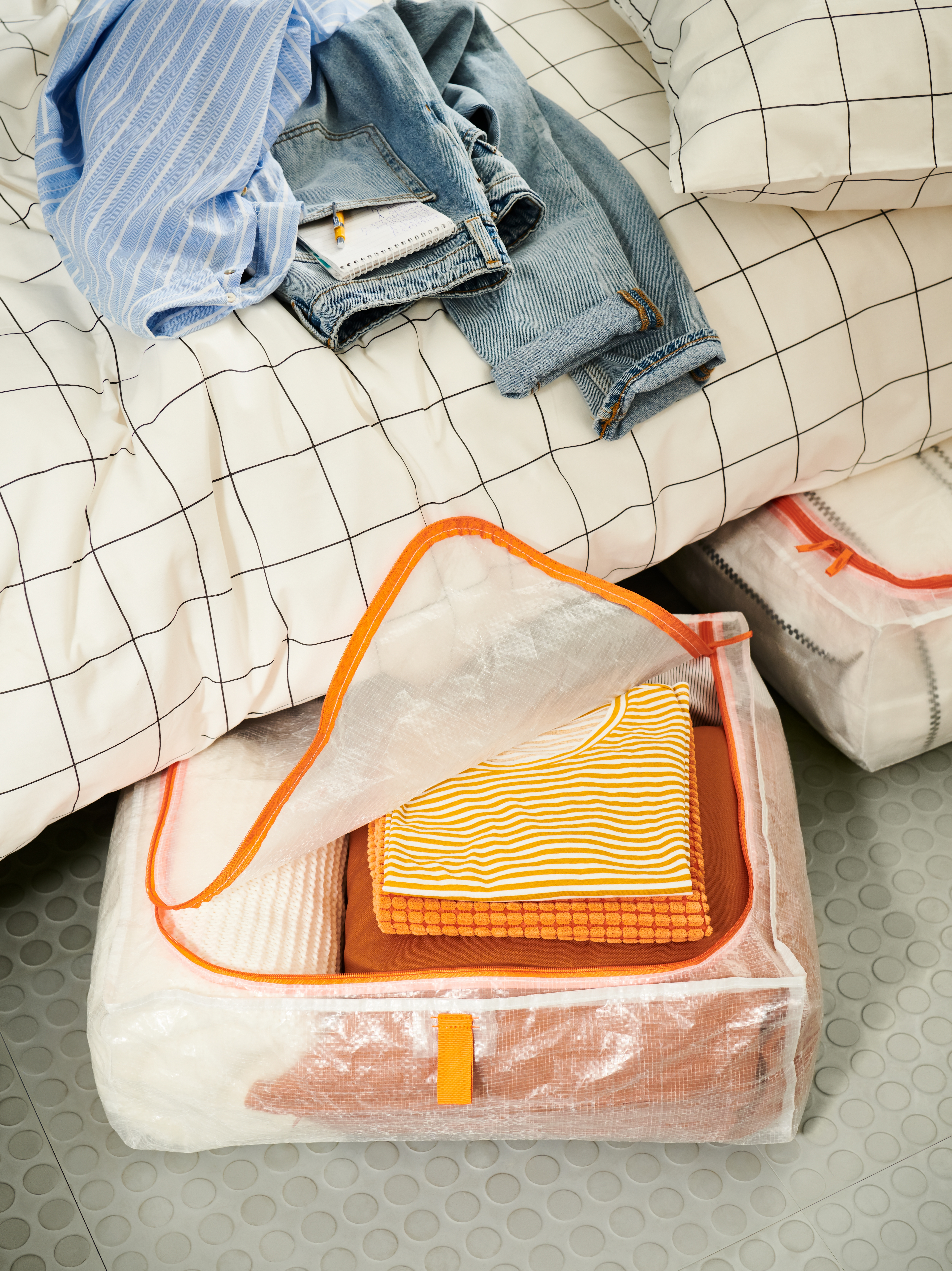 Two storage cases with orange zips sticking out from under a bed made with a white quilt cover with a black-patterned grid.