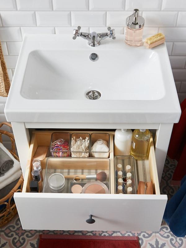 Un meuble lavabo blanc avec un tiroir ouvert contenant des boîtes GODMORGON fumées qui abritent des produits et accessoires de beauté.