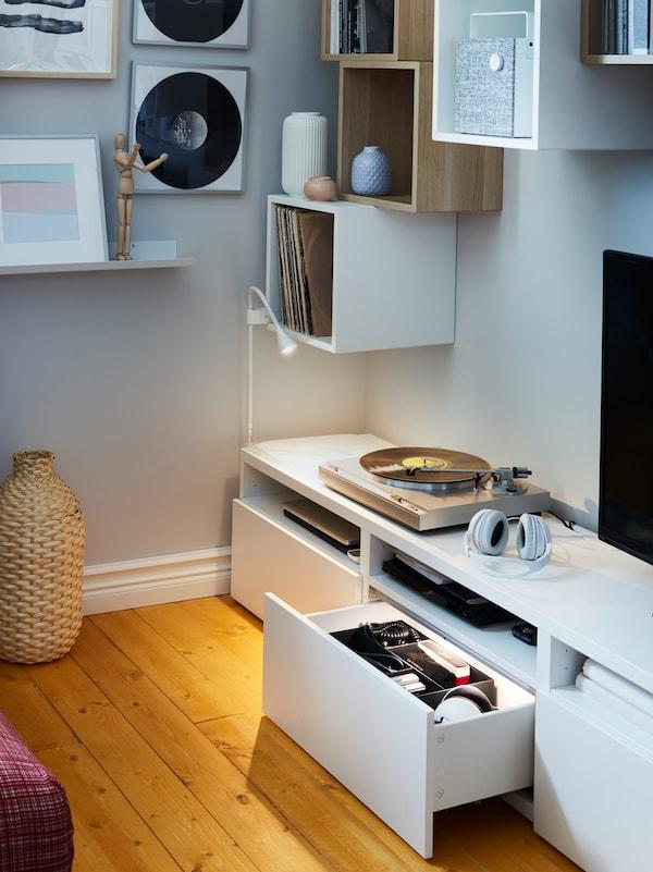 Eine weisse TV-Bank mit geöffneter und beleuchteter Schublade, u. a. mit weissen Wandschränken, einer kleinen Wandleuchte und einer Dekovase aus Bambus.