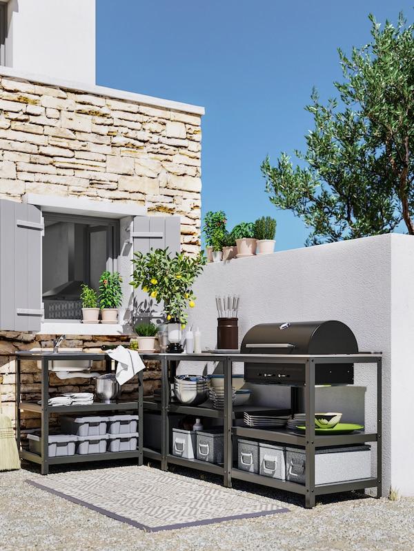 Eine schwarze Küche für draussen an einer Wand mit Fenster, u. a. mit einem Grill, Spüle und Ablagen mit Geschirr und Küchenutensilien.