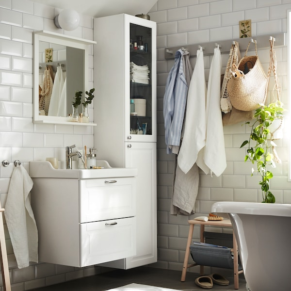 A white bathroom with a white wash-stand with 2 drawers below a white mirror with shelf next to a white high cabinet.