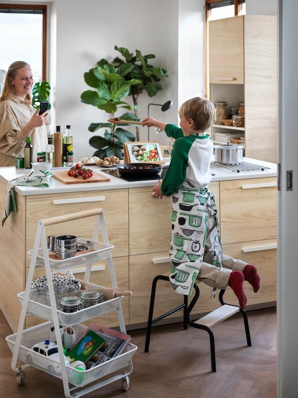 Esquina de una cocina con un carrito RISATORP blanco con cazos y utensilios en la esquina de una cocina, donde hay una mujer y un niño cocinando.