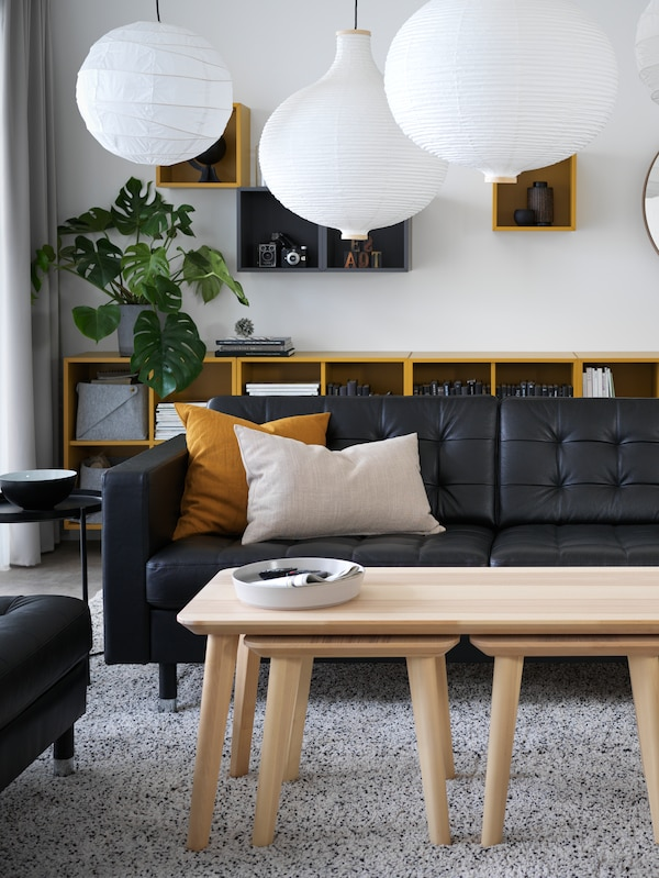 A living room with furniture including LANDSKRONA sofa, EKET storage cabinets, LISABO tables and RISBYN lampshades.