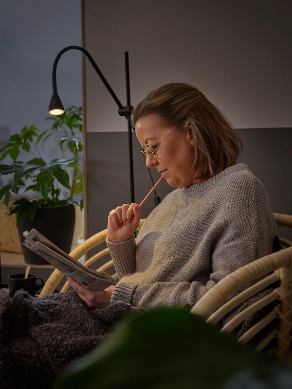L'éclairage d'un lampadaire NÄVLINGE aide une femme assise dans un fauteuil BUSKBO à se concentrer et à trouver des indices pour terminer ses mots croisés.