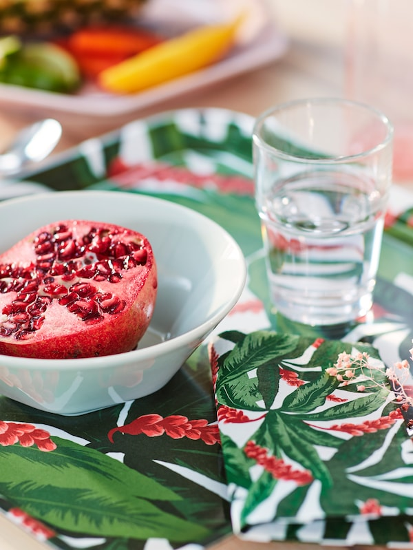 Table with a halved pomegranate in a white bowl placed on a red and green SOMMARLIV tray and matching napkin.