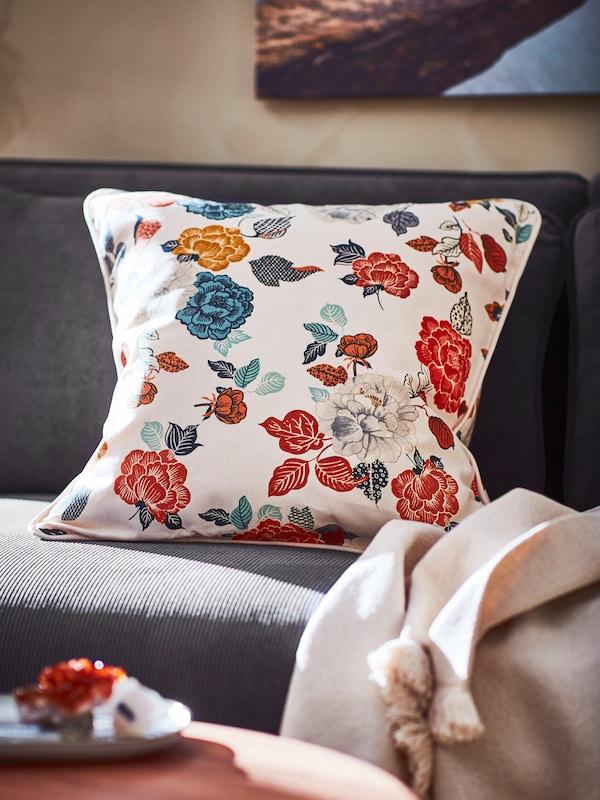 Nahaufnahme eines Kissens mit buntem Blumendruck auf einem grauen Sofa.