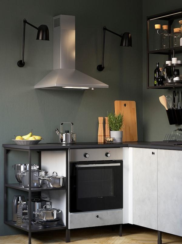 Una cocina ENHET con armarios grises contra una pared verde con un extractor montado en la pared y dos lámparas de techo negras.