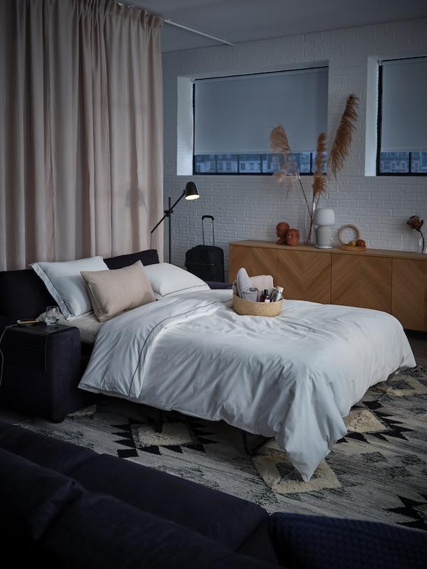 Katil sofa 2 tempat duduk, langsir penghalang cahaya berwarna kuning air, kuilt dan bantal, bakul alu-aluan yang berisi tuala dan kelengkapan dandanan diri.